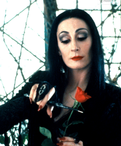 Morticia Addams cuts the head off a rose